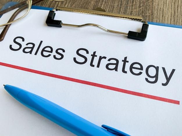 Papel con estrategia de ventas de texto en la mesa de madera.