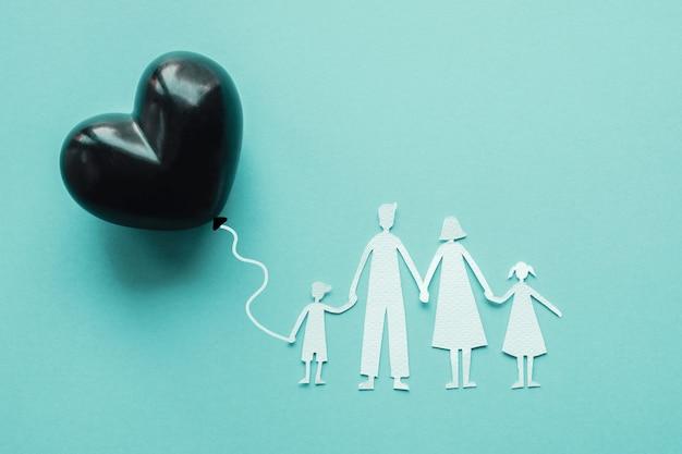 Papel familiar recortado sosteniendo globo corazón negro sobre fondo azul.