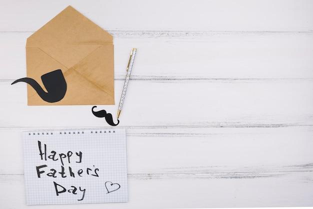 Papel con feliz título del día del padre cerca de bigote de adorno y pipa humeante en letra
