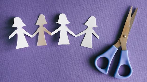 Papel de figuras femeninas y tijeras.