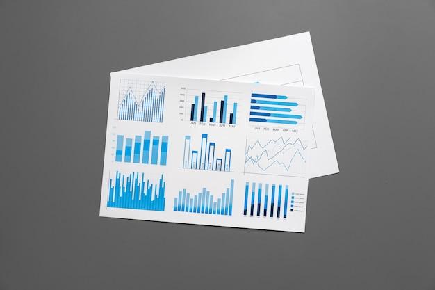 Papel financiero con gráficos y diagramas en mesa gris