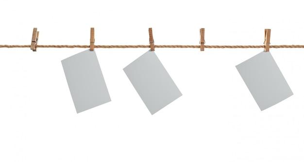 Papel fotográfico blanco. colgando de un tendedero con pinzas para la ropa.