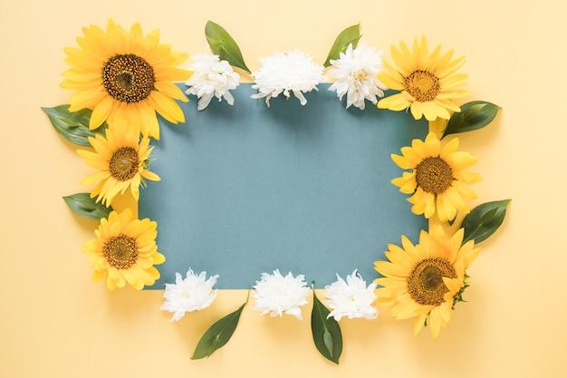 Papel gris en blanco rodeado de flores sobre fondo amarillo
