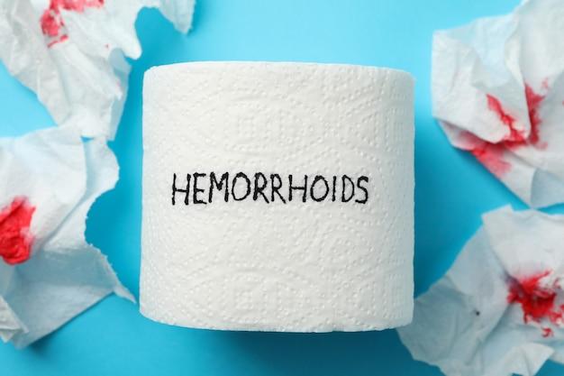 Papel higiénico con hemorroides y papel con sangre en azul, primer plano