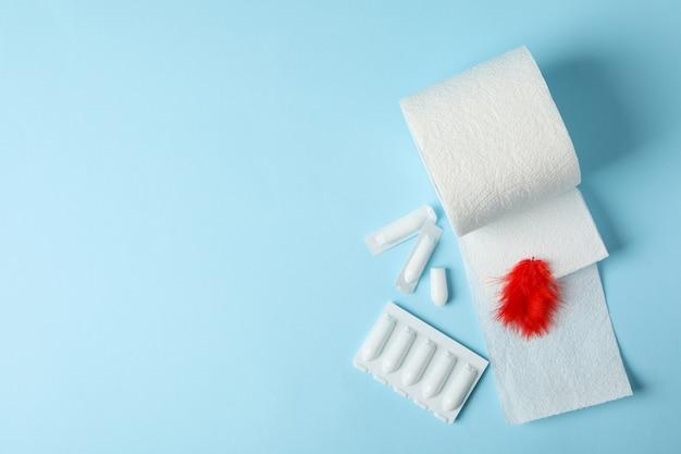 Papel higiénico, plumas y velas en azul. hemorroides