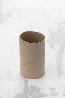 Papel higiénico vacío sobre la superficie de cerámica gris