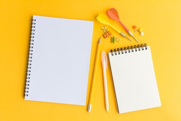 Papel y lápiz en blanco sobre fondo amarillo