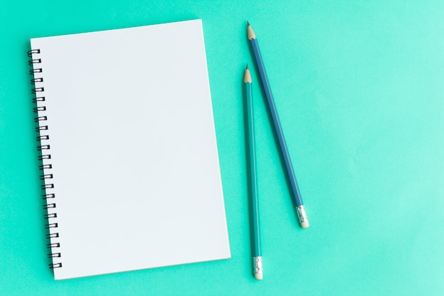 Papel y lápiz en blanco sobre verde