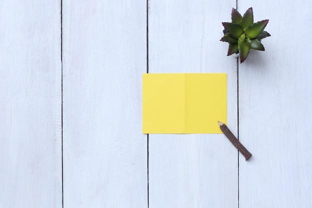 El papel, el lápiz y la maceta del amarillo de la visión superior en el piso de madera blanco y tienen espacio de la copia.