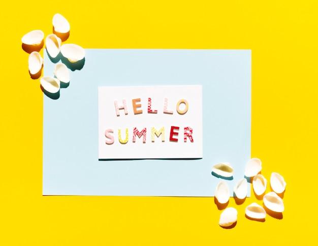 Papel con letras hola verano y conchas marinas.
