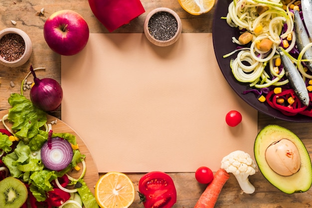 Papel marrón rodeado de saludables vegetales picados; frutas ingredientes en la mesa