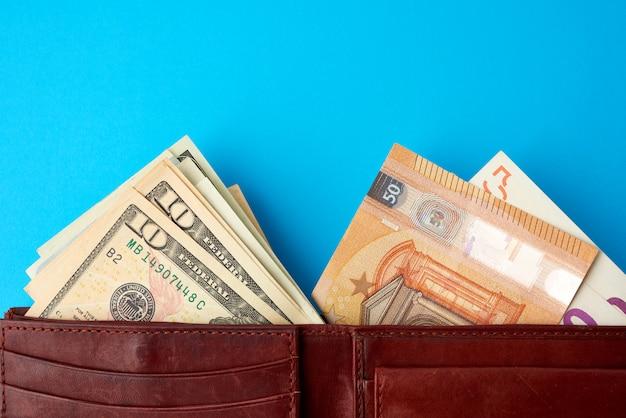 Papel moneda de la unión europea euro y dólares estadounidenses en cuero marrón