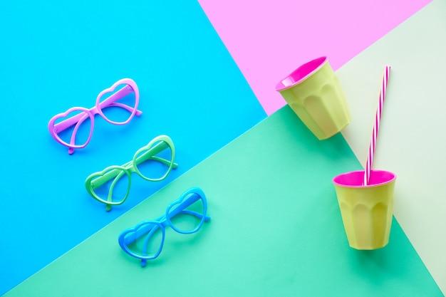 Papel multicolor en colores pastel, vista superior de gafas o gafas de sol en forma de corazón y vaso de plástico con paja. geométrica diagonal creativa endecha plana.