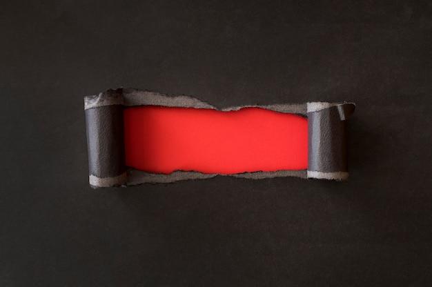 Papel negro rasgado abstracto que revela papel rojo