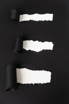 Papel negro rasgado que revela blanco