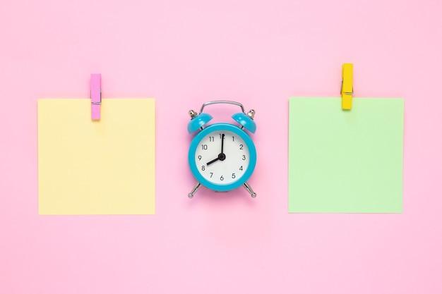 Papel de nota con alfiler y reloj despertador en rosa, plano