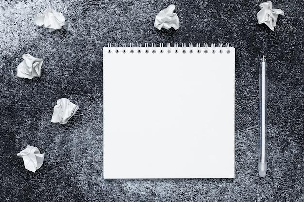Papel de nota en blanco sobre fondo de tablero negro. cuaderno de espiral y bolígrafo blanco. copie el espacio para el texto. .