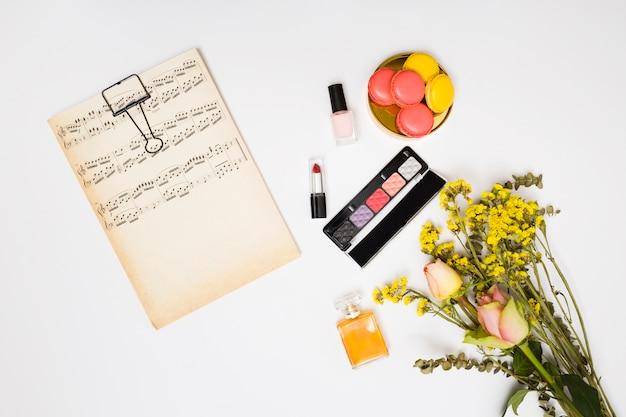 Papel de notas musicales vintage; lápiz labial; botella de esmalte de uñas; botella de perfume; ramo de flores y macarrones sobre fondo blanco