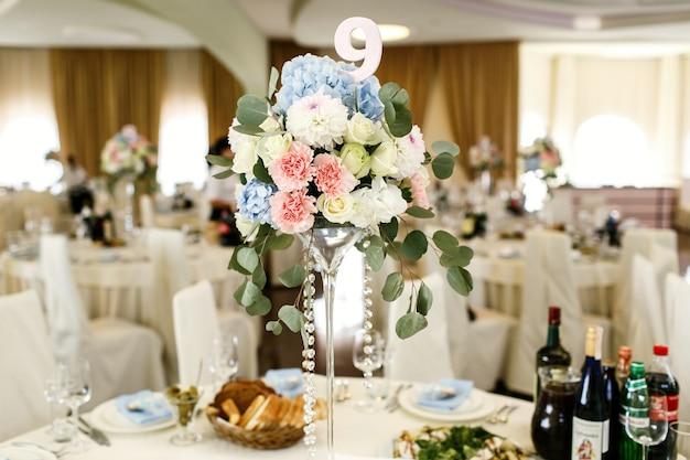 Papel número 9 puesto en un ramo de flores rosas y azules