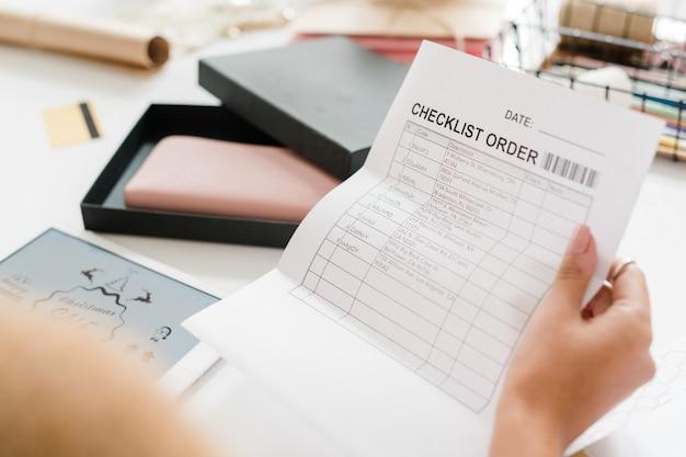 Papel con orden de lista de verificación en poder de una joven compradora mirando a través de posiciones con productos ordenados sobre el escritorio