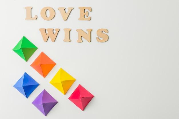 Papel origami en colores lgbt y amor gana palabras.