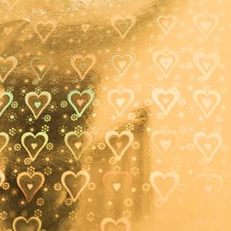 Papel de oro con patrón de corazones.