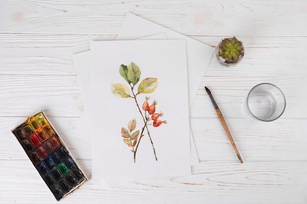Papel con pintura vegetal cerca de vidrio, pincel y acuarelas.