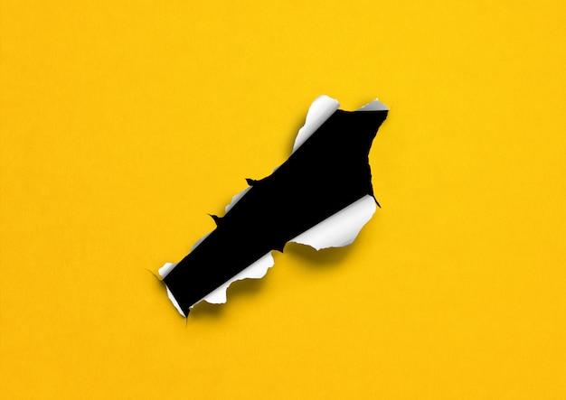 Papel rasgado amarillo con agujero negro