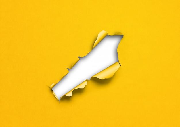 Papel rasgado amarillo con agujero
