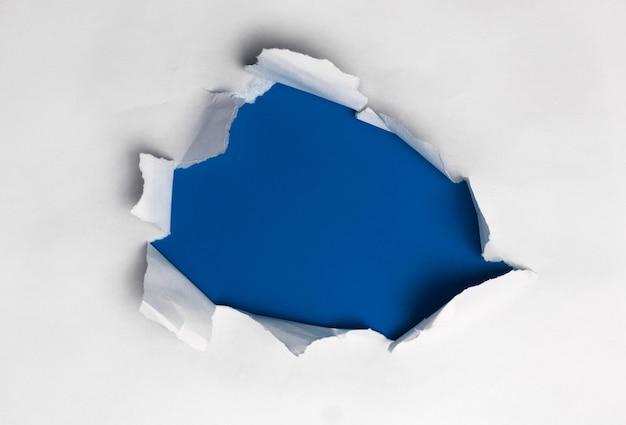 Papel rasgado blanco sobre fondo azul.