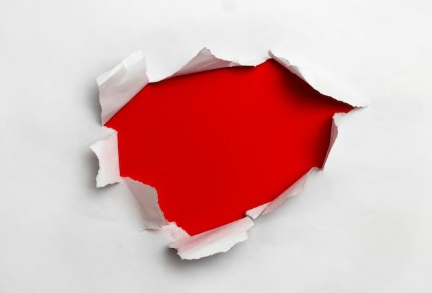 Papel rasgado blanco sobre fondo rojo.