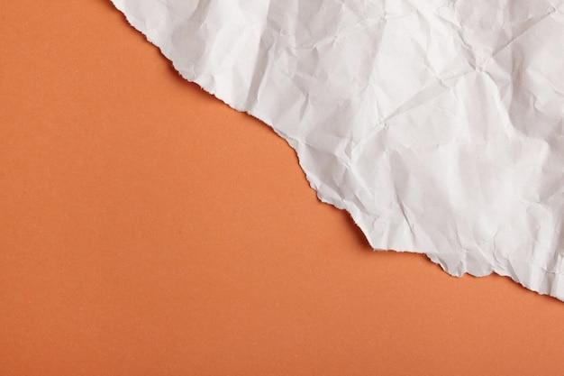 Papel rasgado de color naranja y blanco.