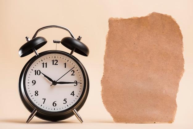 Papel rasgado marrón en blanco cerca del reloj de alarma negro contra el telón de fondo de color