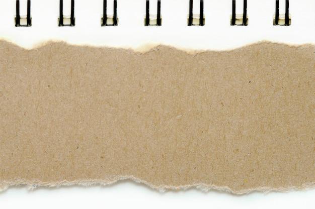 Papel rasgado marrón sobre fondo de color de papel blanco de libro