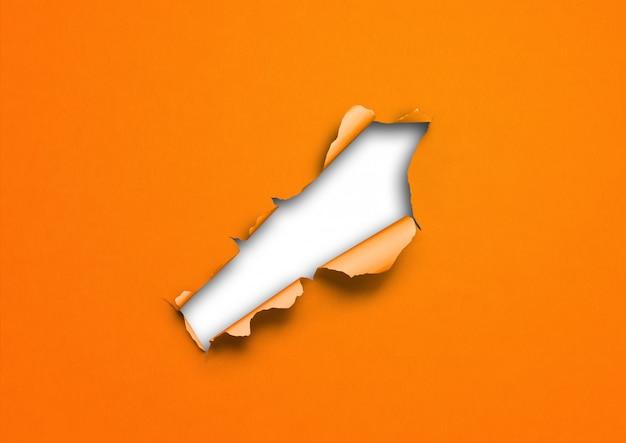 Papel rasgado naranja con fondo de agujero