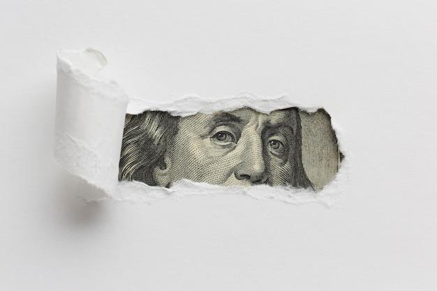 Papel rasgado que revela billete de un dólar