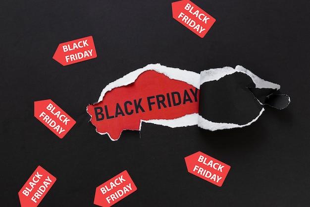 Papel rasgado que revela el texto del viernes negro con pegatinas