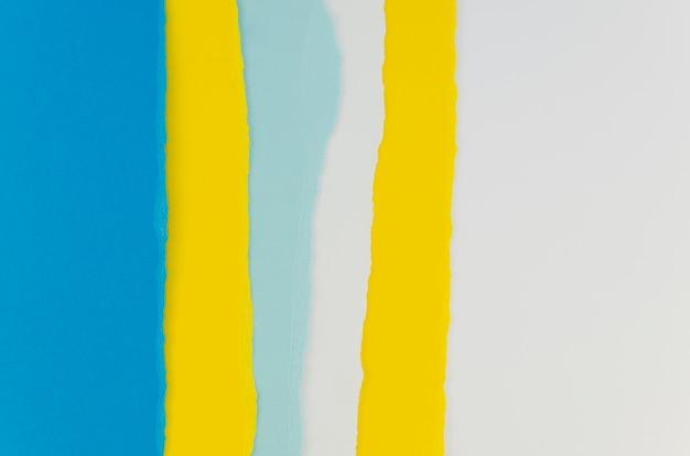 Papel rasgado en tonos amarillos y azules.