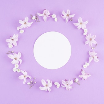 Papel redondo blanco en marco de flores.
