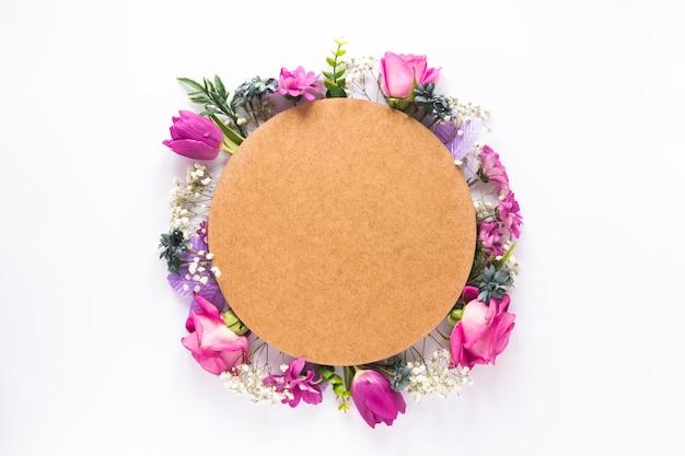 Papel redondo sobre diferentes flores en mesa.