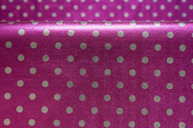 Papel de regalo brillante púrpura con lunares con un pliegue, papel de aluminio para el diseño de envoltura de regalos, papel tapiz, elegante textura brillante