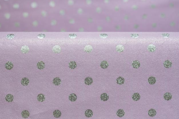 Papel de regalo brillante violeta con lunares con un pliegue. lámina para envoltura de regalos, papel tapiz. elegante textura brillante