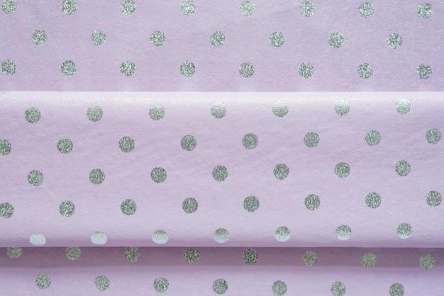 Papel de regalo brillante violeta con lunares con un pliegue, papel de aluminio para el diseño de envoltura de regalos, papel tapiz, textura brillante con estilo