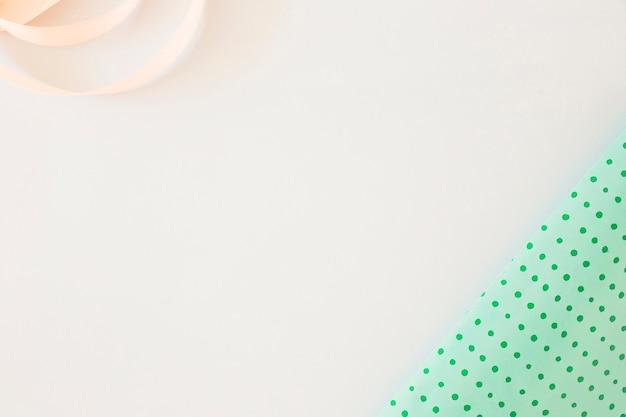 Papel de regalo y cinta de raso rizado sobre fondo blanco