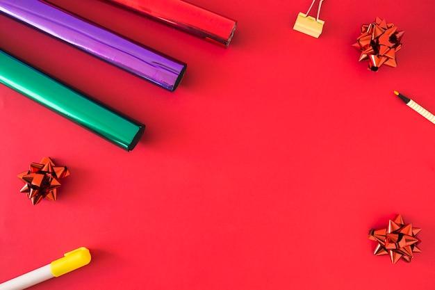 Papel de regalo enrollado; arco; rotulador y pin de bulldog sobre fondo rojo