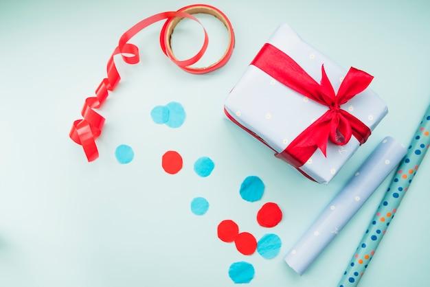 Papel de regalo enrollado; listón rojo; y presente en fondo azul