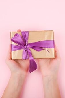 Papel de regalo en manos de una niña, vista desde arriba. endecha plana sobre fondo rosa, la mujer da un regalo para navidad o cumpleaños