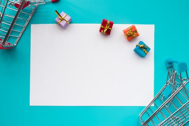 Papel rodeado de mini regalos y carrito de la compra