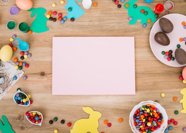 Papel rosa en blanco rodeado de chocolates; conejito de pascua y caramelos de gemas en el escritorio