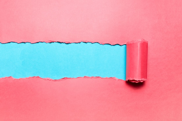 Papel rosa diagonalmente rasgado con espacio para texto de fondo cian.